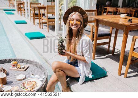 Stunning Tanned Female Tourist Smiling Near Pool. Adorable Fair-haired Girl Holding Pineapple Cockta