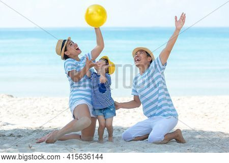 Asian Happy Family Have Fun And Play Yellow Ball On The Beach.  Family People Tourism Travel In Summ