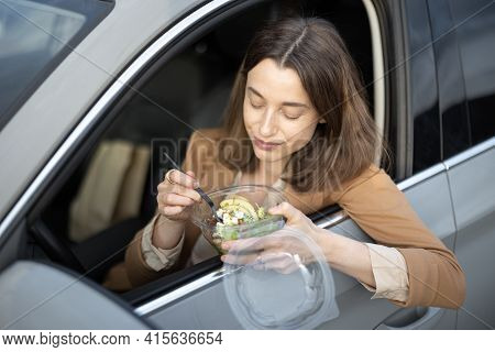 Beautiful Woman Eating Heathy Salad In The Car. Received A Food Order To Go. Have A Quickly Snack On