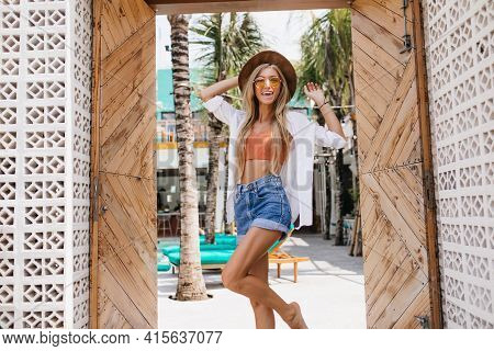 Gorgeous Woman With Inspired Face Expression Dancing Near Wooden Door. Outdoor Portrait Of Attractiv