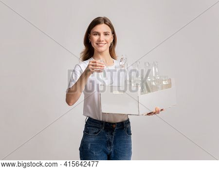 Reuse Of Waste Materials. Smiling Woman Holding Box With Empty Glass Bottles