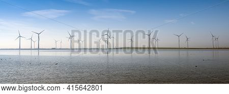 Wind Turbines Under Blue Sky On Philipsdam In Dutch Province Of Zeeland In The Netherlands In The Ne