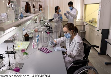 Chemist in mask examining liquid in test tubes while working with her colleagues in the laboratory