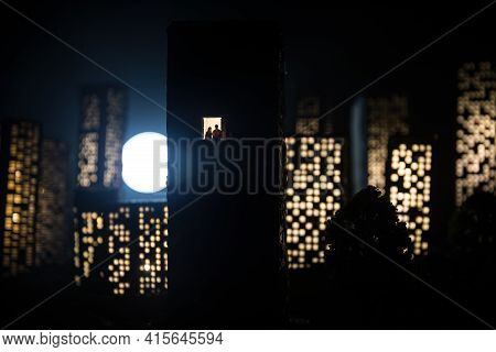 Concept Of Loneliness, In The Form Of A Silhouette Of Woman And Man In A City Window At Night. Symbo
