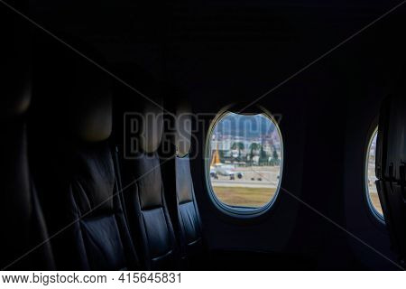 Dark Airplane Interior. Three Free Seats By The Window. Airplane Before Departure.