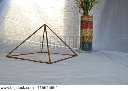 Copper Pyramid With Lighting, With Antique Glass Vase And Stones In Side View, With Natural Backgrou