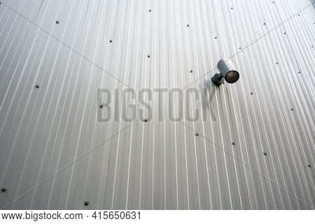 Spot Light Hanging On Metal Sheet Wall On Outdoor Public Area.