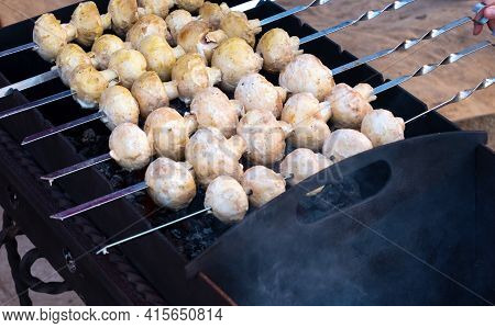 Champignons Fried On A Skewer Over An Open Fire On The Grill. Cooking For A Holiday In The Open Air.