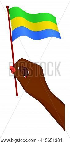 Female Hand Gently Holds Small Flag Of Gabon. Holiday Design Element. Cartoon Vector On White Backgr