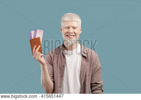 Cheap Flights Concept. Happy Albino Man Holding Passport And Tickets, Standing Isolated On Turquoise