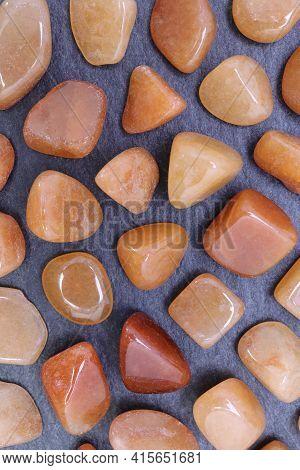 Red Aventurine Rare Jewel On Black Stone Texture. Sparse Mineral Pebbles Background.