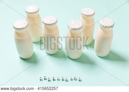 Small Bottles With Probiotics And Prebiotics Dairy Drink On Blue Background. Production With Biologi
