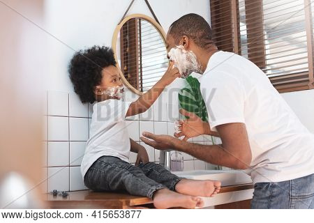 Cheerful African American Man And Little Boy Having Fun Laughing With Shaving Foam On Their Faces In