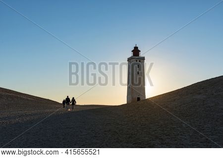 Several people walking up to the old lighthouse of Rubjerg Knude to enjoy the sunset from the top of the dune