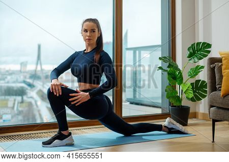 Young brunette in tracksuit practices yoga standing in warrior position on floor mat by window with city view on glazed balcony