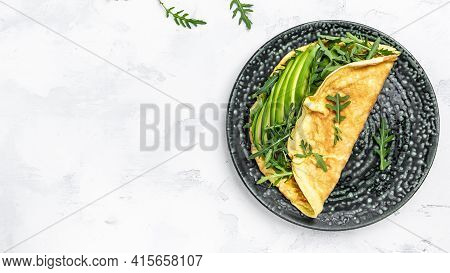Stuffed Omelette With Avocado And Arugula On Light Background, Healthy Diet Food For Breakfast. Tast