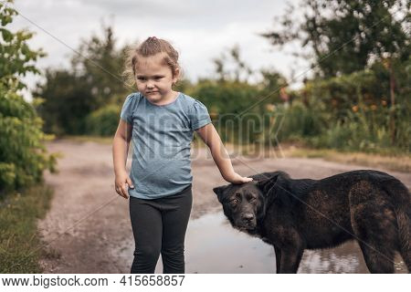 Little Girl Stroking A Big Black Stray Dog In The Street.