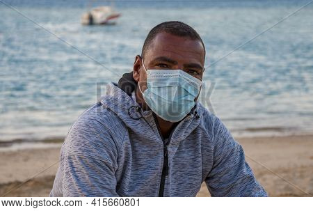 Portrait Of An Egyptian Man About 40 Years Old In A Hoodie And A Medical Mask On The Background Of A