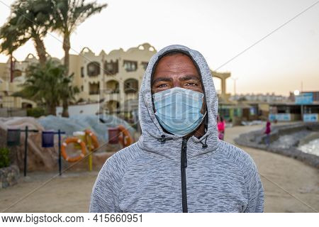 Portrait Of A 40-year-old Black Man Wearing A Medical Mask On An Outdoor Tourist Beach. Perhaps He W