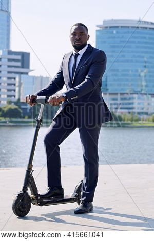 Young serious African businessman in formalwear standing on electric scooter by riverside against group of tall modern buildings