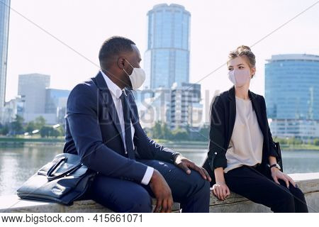Two young intercultural business partners in formalwear and protective masks sitting in urban environment while discussing working points