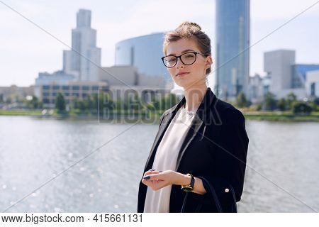 Young confident businesswoman in smart casualwear and eyeglasses looking at you while standing by riverside against cityscape