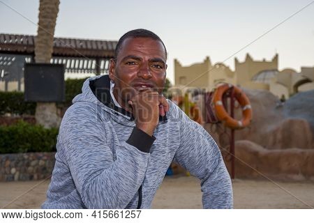 Portrait Of A Dark-skinned Man Of 40 Years On An Open Tourist Beach Against The Background Of Lifebu