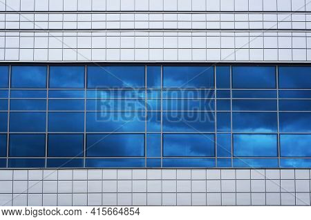 Facade of modern building. Reflection of sky in windows glass. Abstract architectural background.