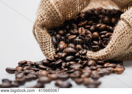 Hessian Sack Bag With Blurred Roasted Coffee Beans Isolated On White.