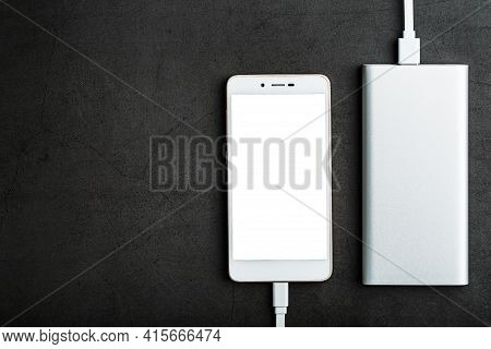 White Smartphone Is Being Charged From The Power Bank On A Black Background. Top View, Free Space
