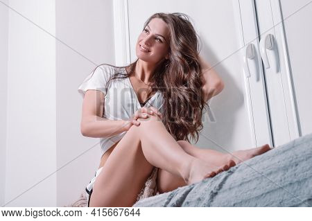 Charming Brown-haired Woman With Long Curly Hair Posing Near The Window. Healthy Hair Concept.