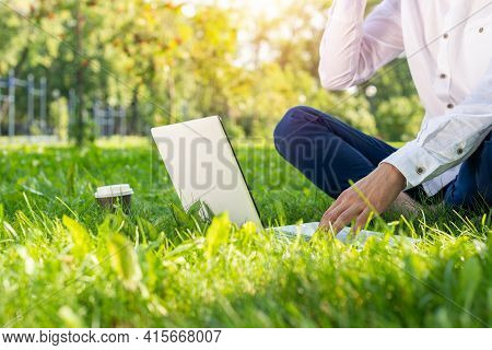 Businessman Using Laptop Computer On Green Grass In Park. Close Up Man Hands Typing On Keyboard. Man
