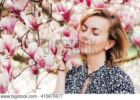 Portrait Of A Beautiful Woman In Her Forties. Profile Portrait With A Pink Flowering Magnolia Tree A