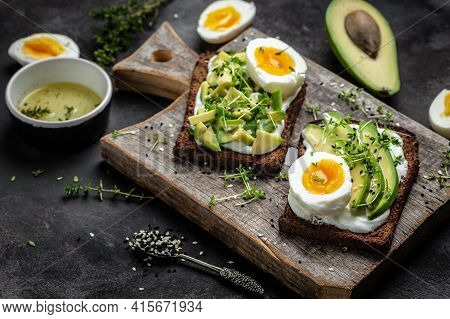 Rye Toasts With Soft Cheese, Avocado And Boiled Egg With Olive Oil And Bread. Healthy Diet Or Vegeta