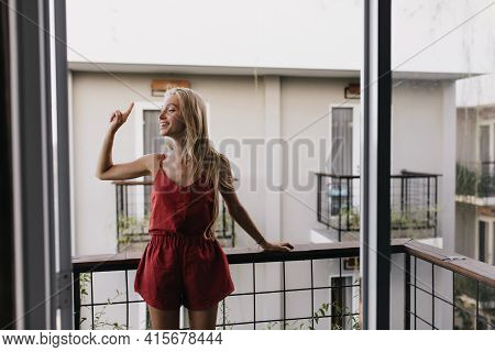 Good-humoured Female Model With Blonde Hair Standing At Balcony. Winsome Tanned Girl In Red Pajama E