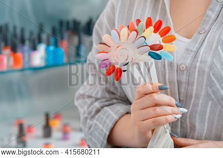 Female Hands With Artificial Acrylic Nails Picks Up New Polish Color For Manicure Design. Assortment