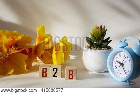 B2b Word Letters On Wooden Blocks. Clock, Cactus And Yellow Branch On A White Background .business C
