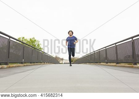 A Young Male Athlete Trains In The Street Running Straight Ahead