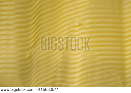 Full Frame Background Texture Of Ripples In Yellow Margarine. Possible Healthier Food Choice To Trad