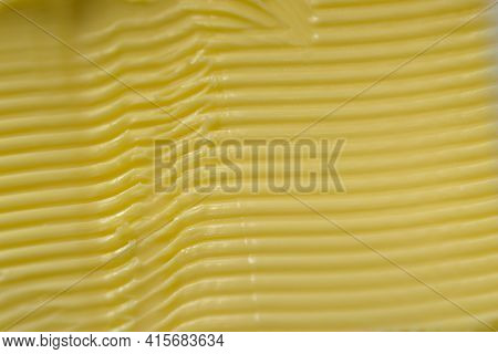 Super Macro Image Of Spreadable Yellow Margarine, After Having A Kitchen Knife Run Through It To Cre