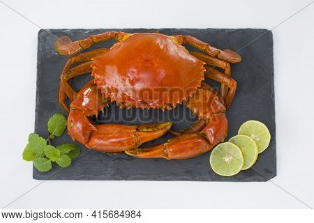 Cooked Mud Crab, Which Is Red In Colour Arranged On A Slate And Garnished With Lemon Slices And Fres