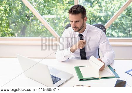 Shot Of Thinking Businessman Sitting At Desk And Using Laptop While Working At The Office