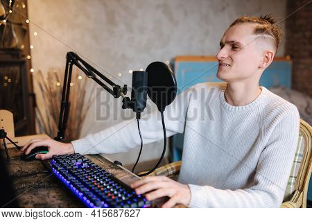 Young Man Makes A Podcast Audio Recording At Home. Man Using Pc And Two Professional Microphones. Pe