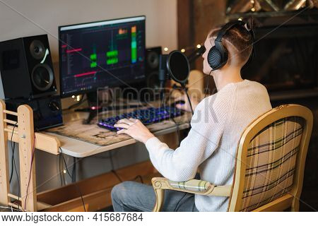 Young Man In Headphones Makes A Podcast Audio Recording At Home. Man Using Pc And Two Professional M