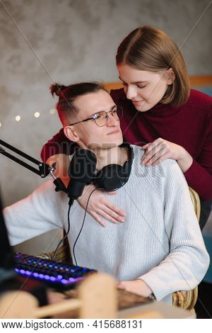 Beautiful Blod Hair Woman Hug His Husband During The Work On Computer. Happy Couple Working At Home.
