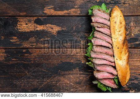 Grilled Baguette Steak Sandwich With Arugula And Cheese. Dark Wooden Background. Top View. Copy Spac
