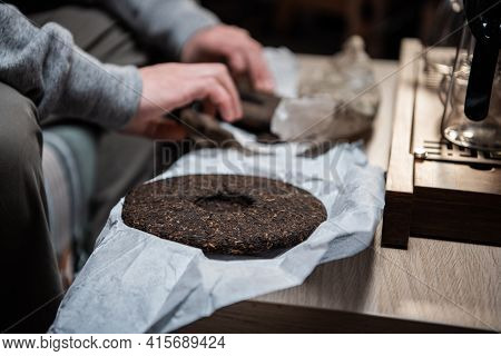 A Piece Of Raw Pu-erh Tea Cake In The Hands Of A Tea Master Before A Real Chinese Tea Ceremony In A