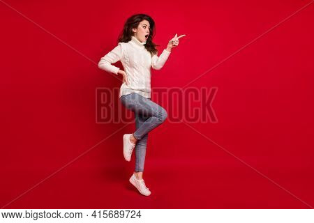 Full Length Photo Of Cute Excited Lady Wear Collar Pullover Pointing Finger Empty Space Jumping High