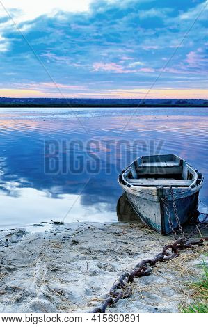 An Old Battered Wooden Boat Is Chained With An Iron Chain To The Riverbank In The Early Morning In T