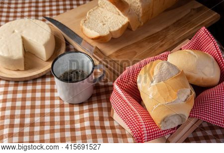 Breakfast Table In Brazil With Breads, Cheese, Cup Of Coffee And Accessories On A Brown And Beige Ch